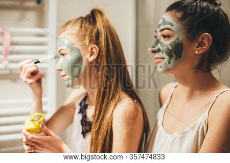 Caucasian Woman With Red Hair And Her Brunette Friend Are Applying A Facial Anti Acne Mask While Loo