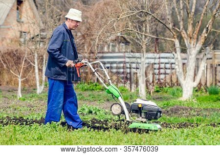A Man Cultivates The Land With A Cultivator In A Spring Garden