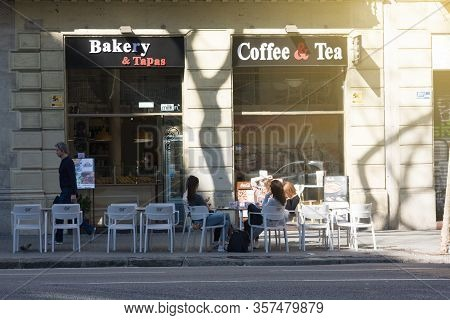 Young Cheerful Girls Have Breakfast In Street Cafe In Sunny Moring. Normal Life Without Quarantine