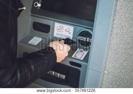 Atm Cash Withdrawal. Woman Using Atm Machine To Withdraw Her Money. Close-up Of Female Hand With Cre
