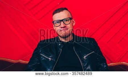 Handsome Young Man With Glasses Makes Discontented Face On Background Red Wall. Portrait Of Adult Yo