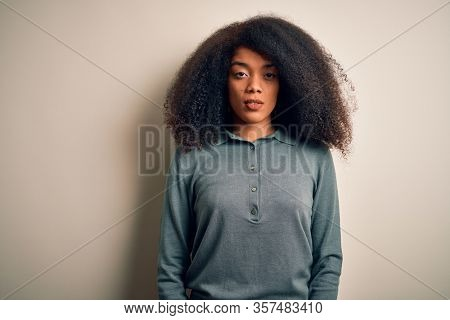 Young beautiful african american woman with afro hair standing over isolated background with serious expression on face. Simple and natural looking at the camera.