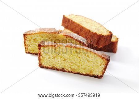 Four pieces of classic sponge cake, biscuit or biscotto isolated on white background. Soft yellow homemade kasutera slices or lemon vanilla loaf pound cakes closeup