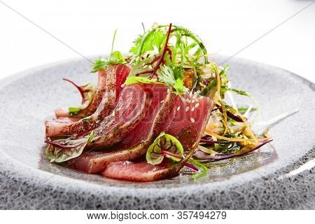 Tataki tuna closeup view. Traditional japanese culinary method. Delicious fish on plate. Tasty sliced seafood with greenery and seasonings. Asian cuisine, food composition. Restaurant dish