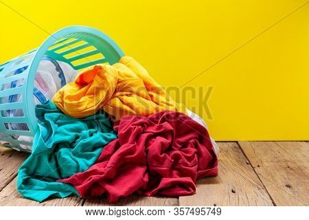 Pile Of Dirty Laundry In Washing Basket On Wooden Plank Yellow Background