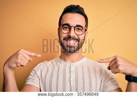 Young handsome man with beard wearing casual t-shirt and glasses over yellow background looking confident with smile on face, pointing oneself with fingers proud and happy.