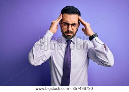 Handsome businessman with beard wearing casual tie and glasses over purple background suffering from headache desperate and stressed because pain and migraine. Hands on head.