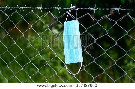 A medical mask hangs on a barbed wire fence. Concept of isolation and quarantine and closed borders of countries during the coronavirus epidemic COVID-19