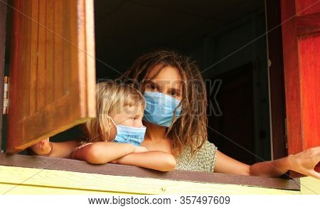 Coronavirus epidemic COVID-19. Mom and daughter in quarantine mask at home in isolation