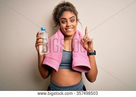 Young african american sporty woman doing sport wearing towel drinking bottle of water surprised with an idea or question pointing finger with happy face, number one