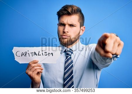 Young blond businessman with beard and blue eyes holding paper with capitalism message pointing with finger to the camera and to you, hand sign, positive and confident gesture from the front
