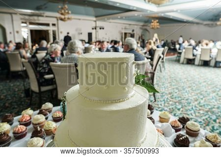 Three tiered wedding cake in foreground with wedding reception out of focus in background.