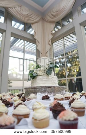 Three tiered wedding cake surrounded by cupcakes at wedding reception.