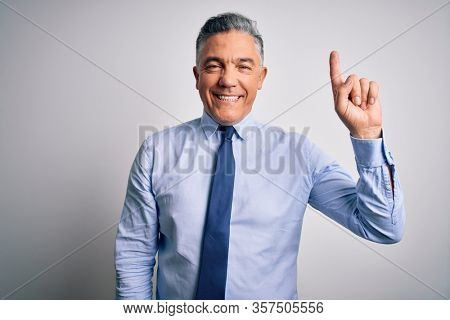 Middle age handsome grey-haired business man wearing elegant shirt and tie showing and pointing up with finger number one while smiling confident and happy.