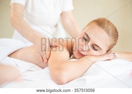 Health Care And Thai Massage. Beautiful Woman Getting Back And Shoulder Massage In Spa Salon