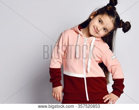 Frolic Sly Smiling Kid Girl With Straight Brunette Hair With Buns In Modern Fashion Pink Brown Hoodi
