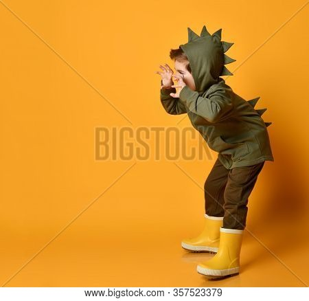 Cheerful Kid Boy In Green Hoodie With Dinosaurus Spikes At His Back And Cowl And Rubber Boots Wellie