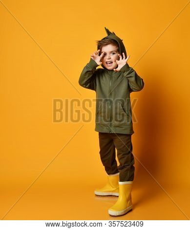 Kid Boy In Green Hoodie With Dinosaurus Spikes At Cowl And Rubber Boots Wellies Plays T-rex Beast Lo