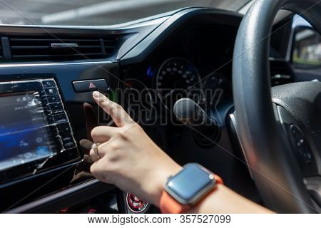 Woman Finger Pressing Emergency Stop Button On Car Dashboard. Driver Pressing On Red Hazard Warning