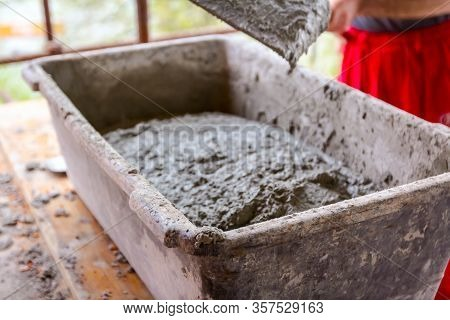 Worker Is Using Shovel To Fill Up With Grout, Mortar Shallow Plastic Container.