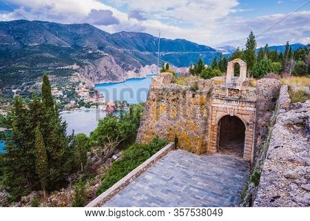 Old Fort Gate On Top Of Frourio Peninsular And Assos Village With Beautiful Sea Bay And Cypress Tree