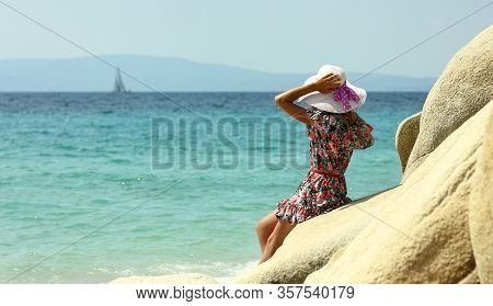 Young Nice Woman In A Hat On The Seashore