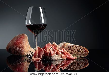 Prosciutto With Ciabatta, Red Wine And Thyme On A Black Reflective Background.  Copy Space.