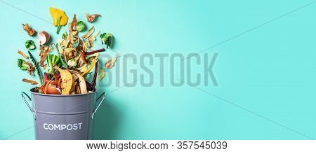 Peeled Vegetables In White Compost Bin On Blue Background. Trash Bin For Composting With Leftover Fr