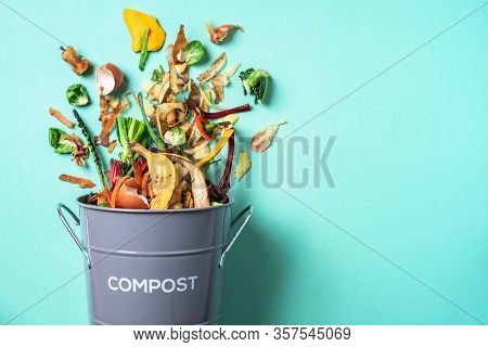 Trash Bin For Composting With Leftover From Kitchen On Blue Background. Top View. Recycling Scarps C