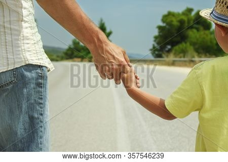 Father And Son Walk Along The Road Holding Hands