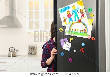 Woman Opening Refrigerator Door With Child's Drawings, Notes And Magnets In Kitchen. Space For Text
