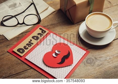 Handmade Card With Words Dear Dad, Gift And Coffee On Wooden Table. Happy Father's Day