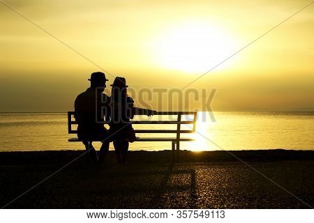 Silhouette Of A Happy Loving Couple At Sunset On The Seashore Bench