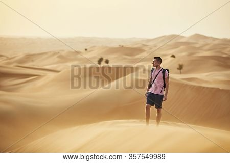 Desert Adventure. Man Standing On Sand Dune. Abu Dhabi, United Arab Emirates
