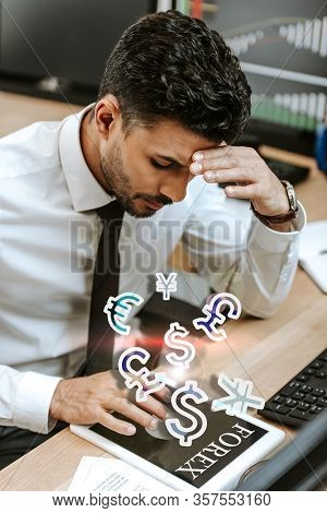 Pensive Bi-racial Trader Using Digital Tablet With Forex Letters