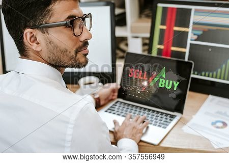 Selective Focus Of Bi-racial Trader Sitting Near Laptop With Sell And Buy Letters