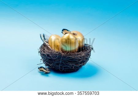 Nest With Gold Decorative Eggs And Feathers In The Nest On A Blue Background. Spring Holiday Concept