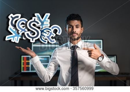Bi-racial Trader Pointing With Finger At Money Signs Near Computes