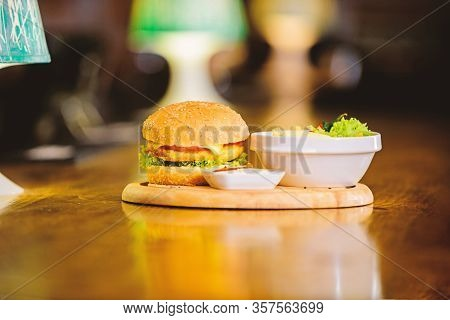 Fast Food Concept. Burger With Cheese Meat And Salad. Cheat Meal. Delicious Burger With Sesame Seeds