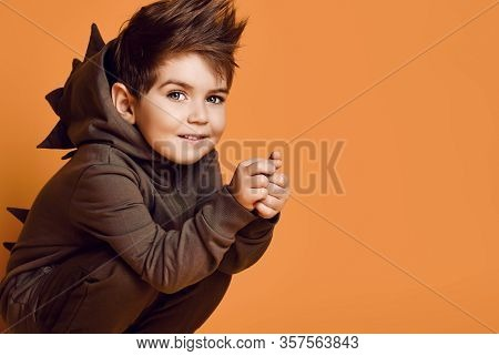 Little Brunet Male In Brown Dino Hoodie With Hood. He Is Smiling, Looking At You While Posing Sittin