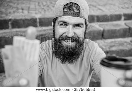 Man Bearded Eat Tasty Sausage And Drink Paper Cup. Street Food Concept. Urban Lifestyle Nutrition. J