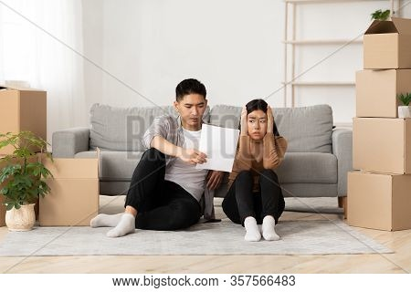 Foreclosure And Repossession Concept. Scared Asian Couple Looking At Eviction Notice, Sitting On The