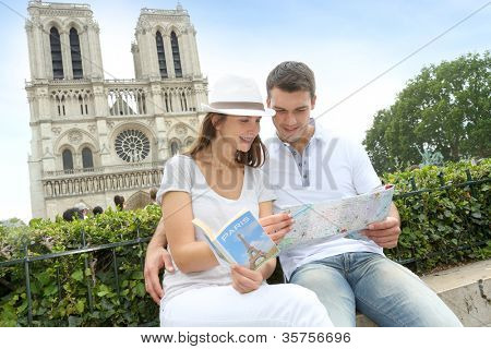 Tourist sitting in front of Notre Dame of Paris Cathedral