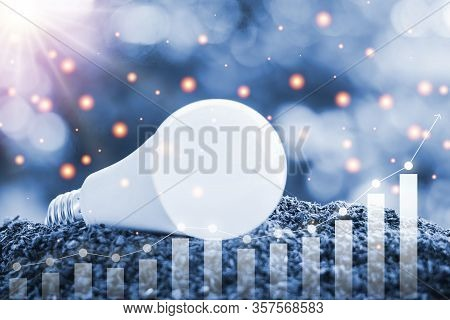 Led Light Bulb On Soil Against Blurred Natural Background With Growing Graph And Light Effect For El