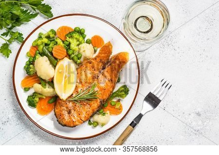Grilled Salmon Fish Steak With Vegetables In White Craft Plate With Wine Glass. Top View On White St