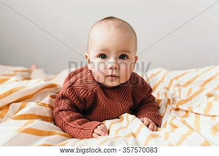 Beautiful Little Baby Girl On The Bed In A Cozy Brown Sweater Smiles. Concept Of Motherhood And Chil