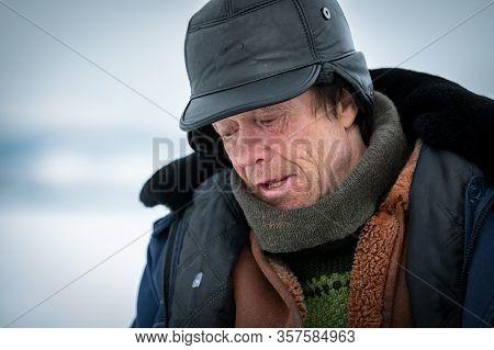 Baikal Lake, Siberia, Russia - March 05, 2020 : Winter Ice Fishing. A Fisherman Is Fishing On Spinin