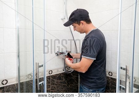 Young plumber man with tools repairing  fixing faucet in shower stall.