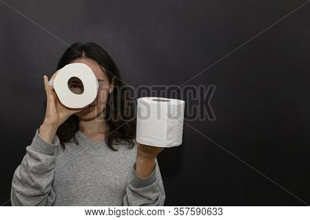Cute Girl Holds Toilet Paper In Her Hands. In One Roll She Looks Like Through Binoculars, The Second