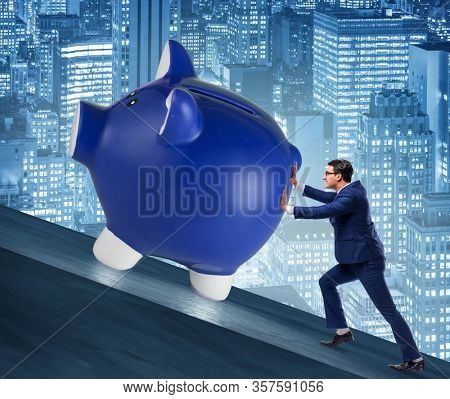 Man pushing piggybank uphill in business concept